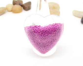 Ring globe heart filled with pink microballs