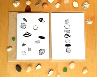 Card with black and white illustration of shells, stones and seeglas. Folded, blank inside, with envelope.