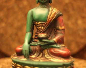 Clay Buddha statue in green in meditation mode