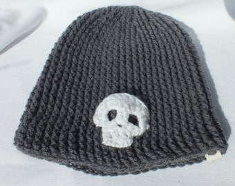 Crocheted beanie hat in grey, with hand crocheted white skull applique.