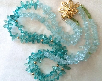Double strand aquamarine, apatite, and peridot necklace with gold flower clasp