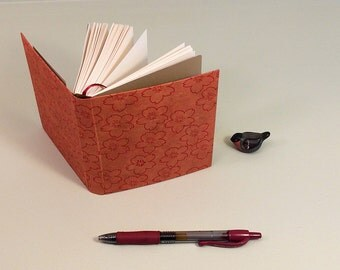 Small journal with red cover and ribbon page marker, plus pocket in back. Mini scrapbook, writing journal, drawing book, handbound book.