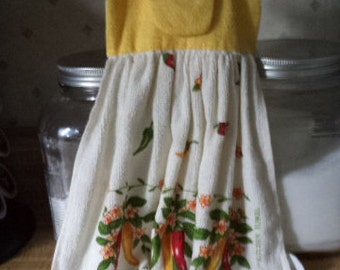 A hang towel in a red and yellow chili pepper cotton terry towel with a bright yellow topper with a velcro closure