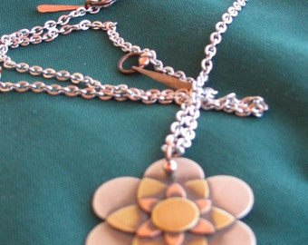 Large Flower tiered metals on steinles silver chain.
