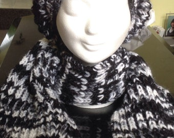 A hand knitted beanie hat and scarf in the colors black and white.
