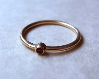 14k gold ring set with garnet stone