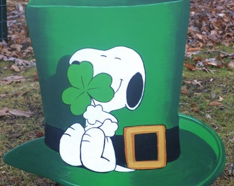 Snoopy hugging a clover on Saint Patricks day sitting on a irishSt. Pattys durby