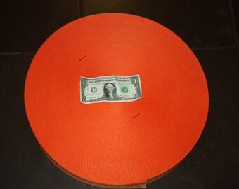Large roll of  orange  webbing with black stiching