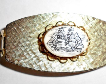 Pretty petite vintage textured goldtone hair clip with faux scrimshaw galleon sailing ship inset