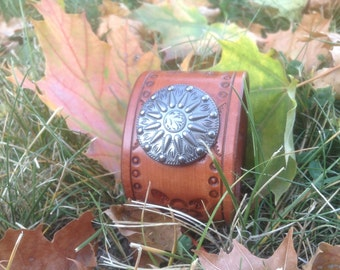 Women's Bandanna print stamped cuff in brown, with Sunburst concho embellishment.