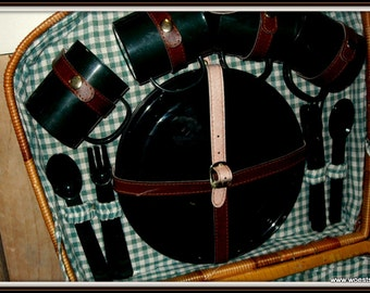 Vintage four person picnic basket of woven reeds. Green wicker basket including green melamine tableware.