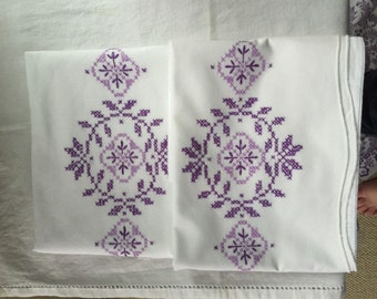 Vintage pillowcases pair with purple crosstitch