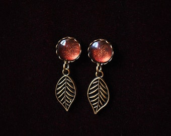Bronze leaf earrings with red shimmering stone