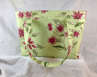 Handbag is fabric with a flowered exterior and a pink striped pillow ticking lining