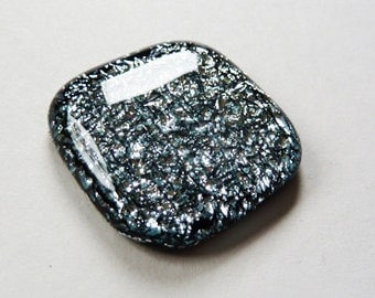 Silver & black cabochon, dichroic fused glass with a very sparkly texture.