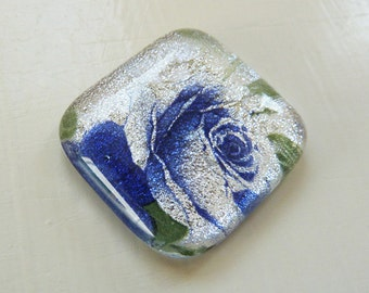 Fused glass cabochon on silver dichroic glass with purple blue rose image.