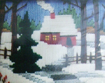 Vintage crewel cottage in the snow