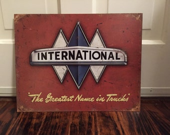 """Reproduction International """" the greatest name in trucks"""" collectible metal sign"""