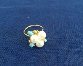 This is a blue, gold, and white pearl ring.