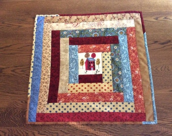 Handmade, quilted log cabin table topper with embroidered center