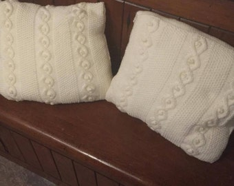 A pair of aran cable cushion covers