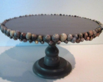 dark gray painted pedestal trimmed with shells
