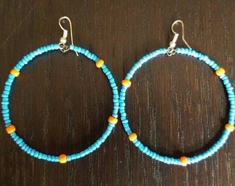 Light blue circular beaded earings with some bright orange beads