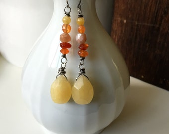 Sunset. Stones the color of a summer sunset are stacked in a neat row. Carnelian, Aventurine and Yellow Jade drop from sterling silver earri