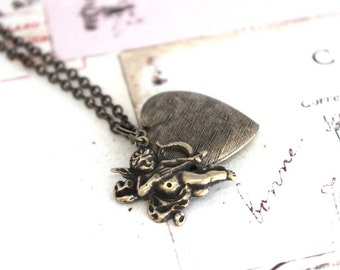 cupid. locket necklace. brass ox with etched lines heart