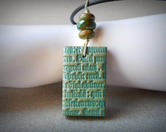 Necklace Gothic Latin polymer clay charm necklace turquoise stones Gutenberg Bible pendant black rubber cord ancient script mystical tribal