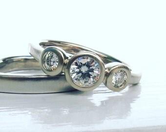 singleB bezel set 3 Stone ring Forever One Moissanite and 14kt white gold