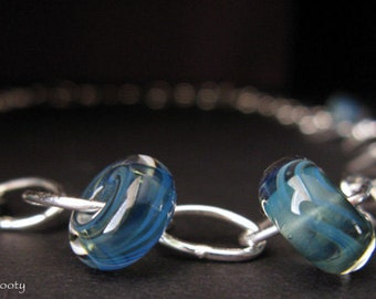 Handmade glass bead necklace. Lampwork boro beads in swirls of blues. Sterling silver handmade chain.  Unique and one of a kind. For her.