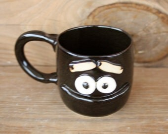 12 Ounce Teacup in Black. Funny Face Mugs. Stoneware Clay Ceramic Pottery. Nelson Studio Ug Chug Face Mug. Unique Uncommon Coffee Cups.