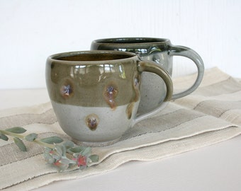His and her cups. Han made, wheel thrown, pottery, altered, earthy, rustic, dimples, celadon, brown, dark gray, polka dots, dishwasher safe