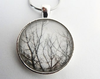 Round pendant necklace with black and white photograph of  tree branches under a glass dome