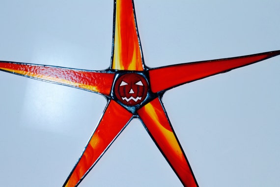 Skinny Jackie- 9 inch stained glass star with striated glass and jack-o-lantern center