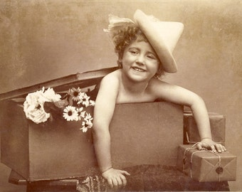 Child with Big SMILE POPS Out of a BOX Full of Flowers Photo Postcard 1908