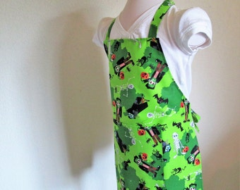 Halloween Childrens Apron filled with spooky Frankies, Draculas, Skeletons, Cat and Bats, a fun apron to create Halloween goodies in