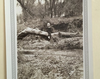 Vintage black and white photo - Toddler sitting on tree over a stream