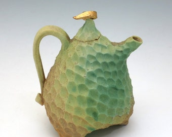 Green and tan porcelain teapot with gold luster on the lid, carved & petite