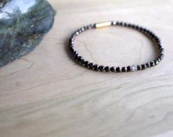 hematite bracelet with tiny faceted stones. labradorite focal stone. gold vermeil back. custom fit stretch bracelet. sparkly charcoal gray.