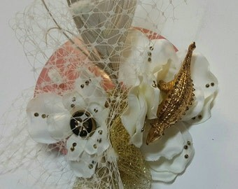 Fascinator with flower and feather in cream gold and pink.