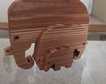 White oak scroll cut three piece Elephant type puzzle that can be displayed flat or spread apart.