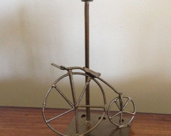 Metal art Big Wheel Bicycle rests on gas light pole, scrap metal recycled metal art, nut and bolt sculpture
