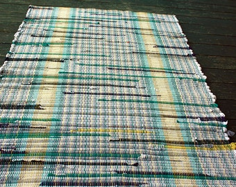 Rag rug in white, teal and yellow.