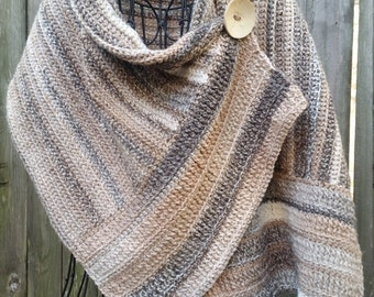 Crocheted buttoned wrap in neutral colors with cream button
