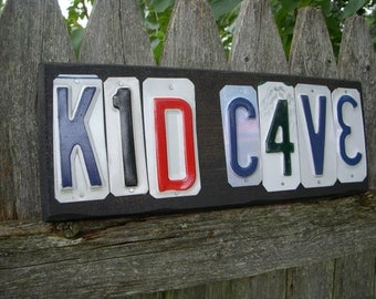 KID CAVE license plate sign.