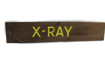 "vintage sign with the word ""X-RAY"" in yellow letters on brown masonite."