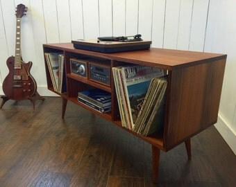 Mid century modern stereo/turntable console or record player cabinet featuring sapele mahogany with tapered wood legs.