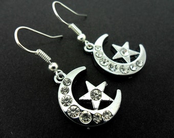 A pair of pretty diamante/ silver plated moon and star dangly earrings.